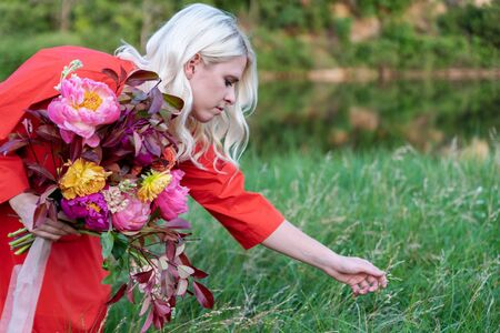 Beautiful young woman with flowers in the field and a lake as a background Фото со стока - 129025778
