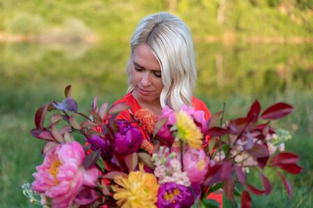 Beautiful young woman with flowers in the field and a lake as a background