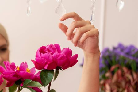 Hands of a beautiful young florist woman making modern bouquet of different flowers Фото со стока