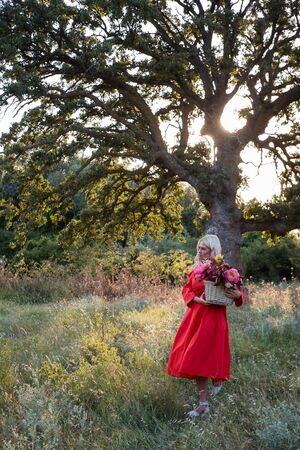 Beautiful young woman with flowers in the field and a tree as a background Фото со стока - 129025792