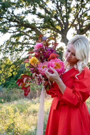 Beautiful young woman with flowers in the field and a tree as a background