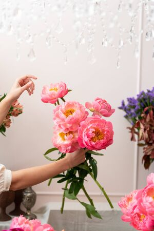 Hands of a young florist woman making modern bouquet of flowers Фото со стока