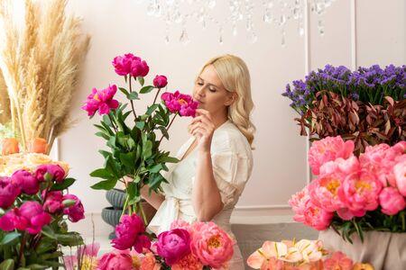 Beautiful blonde florist woman picks up flowers and creates wonderful bouquet Фото со стока - 129025823