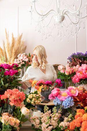Beautiful blonde florist woman picks up flowers and creates wonderful bouquet Фото со стока