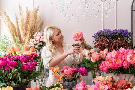 Beautiful blonde florist woman picks up flowers and creates wonderful bouquet Фото со стока - 129025816