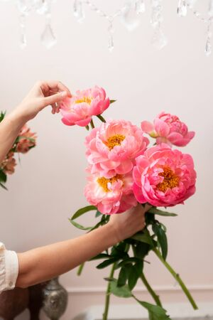 Hands of a young florist woman making modern bouquet of flowers Фото со стока - 129025872