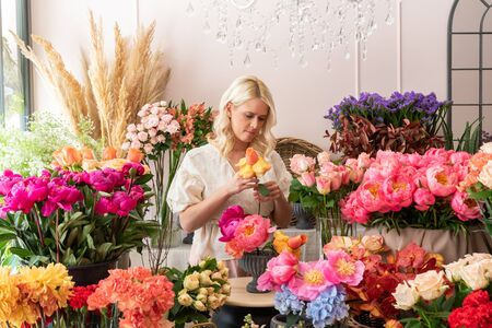 Beautiful blonde florist woman picks up flowers and creates wonderful bouquet Фото со стока - 129025863