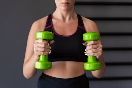 Fitness girl lifting dumbbell in the gym.