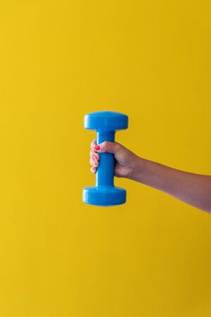 Womans hand holds a dumbbell on a yellow background Фото со стока - 129026112