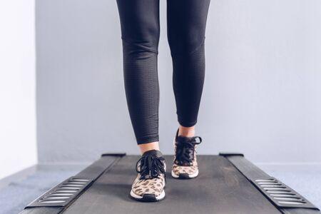 Fitness girl running on treadmill. Фото со стока