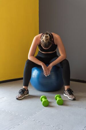 Sport woman sitting and resting after workout or exercise in fitness gym.