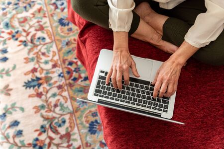 Hands of mature woman using computer at home, top view