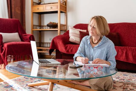 Middle age senior woman working at home using computer