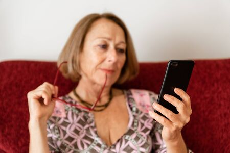 Elegant mature woman using smartphone while sitting on the sofa