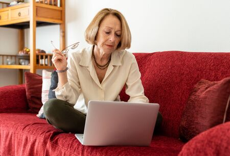 Elegant mature woman using computer at home