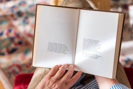 Mature woman is reading a book at home, top view