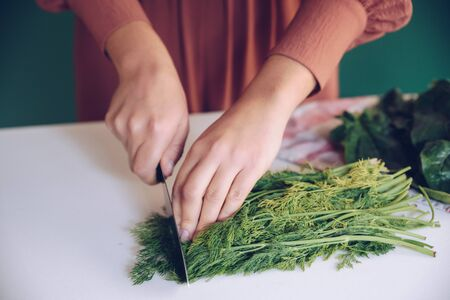 Woman cutting dill on white marble Stok Fotoğraf