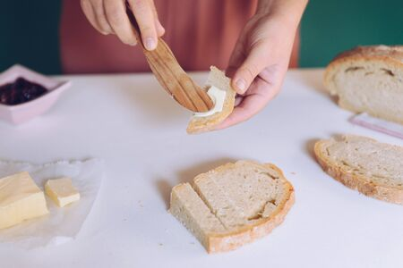 Womans hand spreads butter on homemade bread