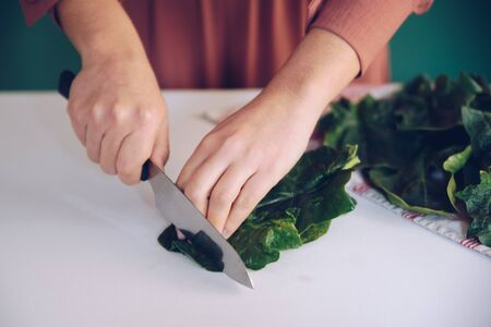 Woman cutting spinach on the marble at her kitchen Stok Fotoğraf