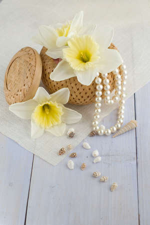 box with pearls, seashells and flowers on light-blue table   photo