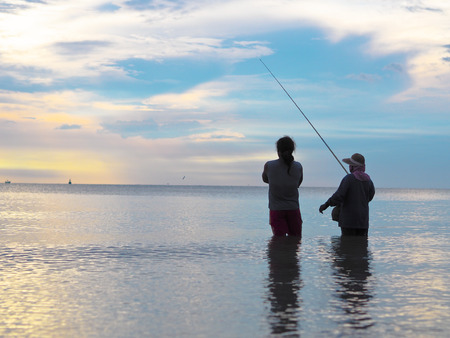 sun rise: they are fishing together in ocean Sun rise form the beach on sunrise