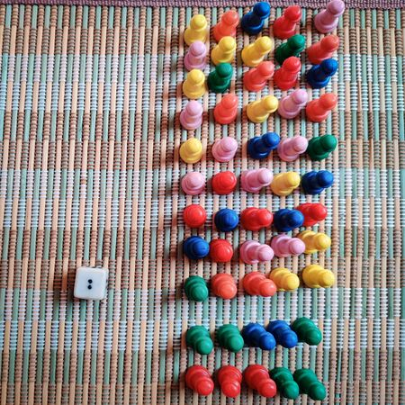 Bunch of colorful game board pieces isolated on mat