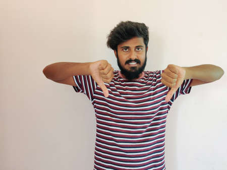 Portrait of a Indian successful beard man in stripped t-shirt showing sign of dislike, isolated on a white background