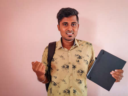 Cheering young south indian with a book in his hand and bag in his shoulder. College concept