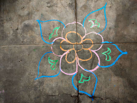 Colorful flower kolam drawn using color chalk pieces. In front of south indian home. Festival time concept.
