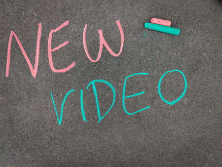 The inscription text on the grey board,NEW VIDEO. Using color chalk pieces.