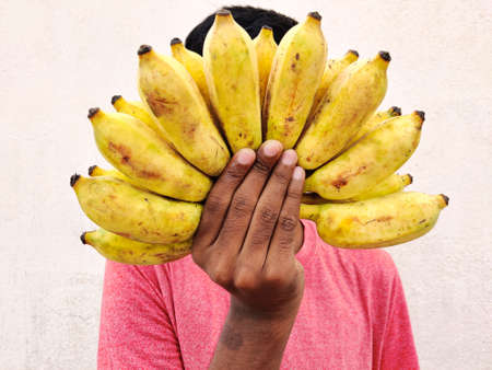 Red tshirt south Indian man covering his face with a cluster of bananas. Isolated on white background. Festival concept