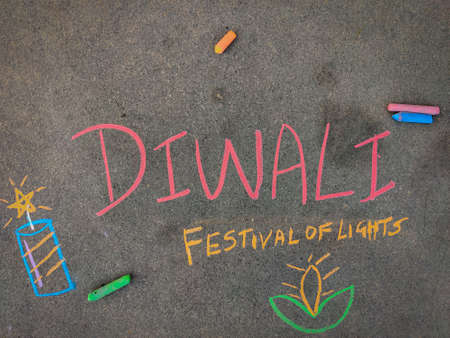 The inscription text on the grey board,Diwali festival of lights with fire crackers and diya lamp. Using color chalk pieces.