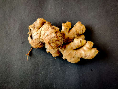 Large piece of fresh Ginger on a black background. Selective focus