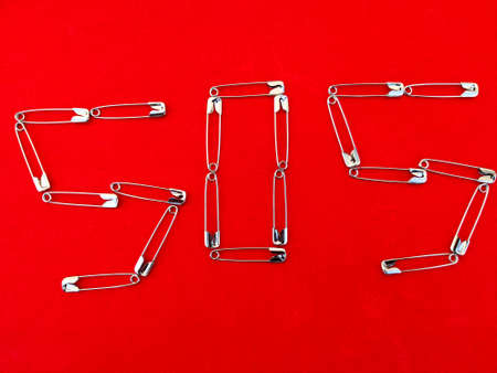 SOS - word drawn using safety pins. Isolated on red background.