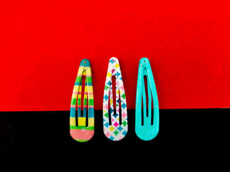 Three colorful patterns of hair clips isolated on red and black background