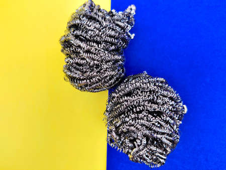 Two stainless steel sponge for dish washing isolated on yellow and blue background.
