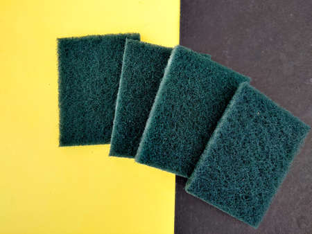 Four green color Scrubber pads for dish washing isolated on yellow and black background.
