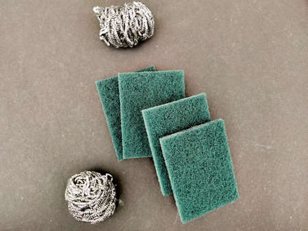 Four Scrubber pads and two stainless steel sponges for washing dishes . Isolated on black background.