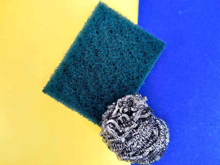 Scrubber pad and stainless steel sponge isolated on yellow and blue background.