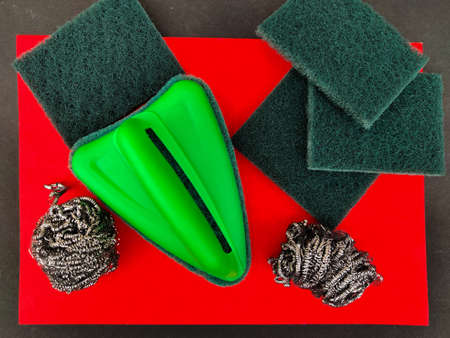 Top view of scrubber pads,stainless steel sponges and bathroom scrubber brush isolated on red and black background.