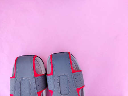 Copy space of one pair of grey and red color men sandals or slipper isolated on pink background