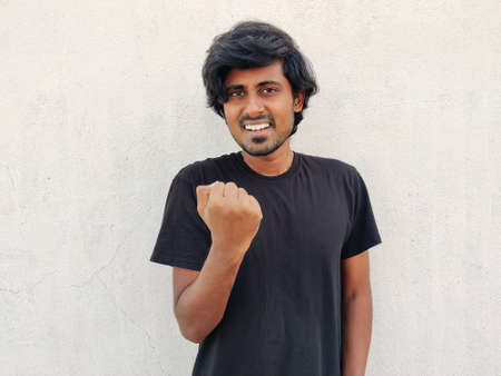 South Indian Young handsome man wearing black tshirt doing winner gesture with one arm raised and smiling. White background