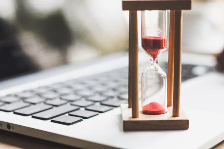 sand clock timer on laptop .symbol of time Stock Photo