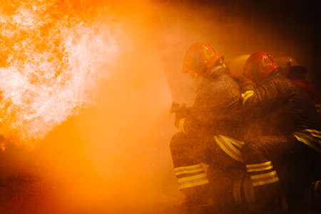 Firefighter training. fireman using water and extinguisher 版權商用圖片