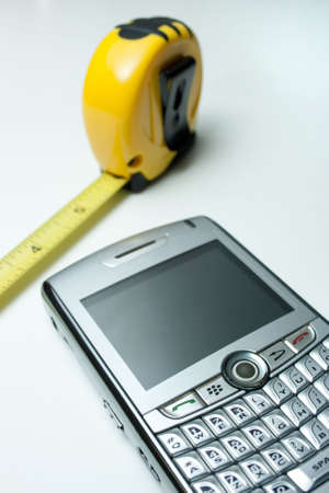 expertise concept: PDA and Tape Measure. Project Tools Stock Photo