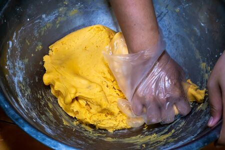 The woman's hand is kneading the dough into the pot to make a snack