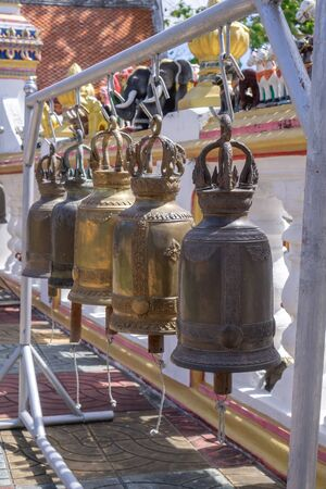 The bell hung on a metal rail near the temple wall.