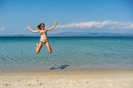 Summertime holiday joy fun jump in Paliouri Beach in Kassandra Sithonia penisula Chalkidiki Greece