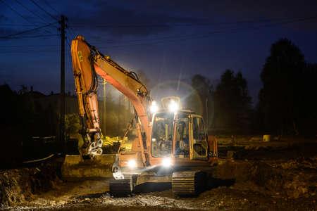 Orange excavator digger working at night on the street