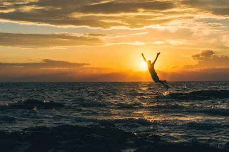 Men jump to adriatic sea durning sunset in Croatia Archivio Fotografico